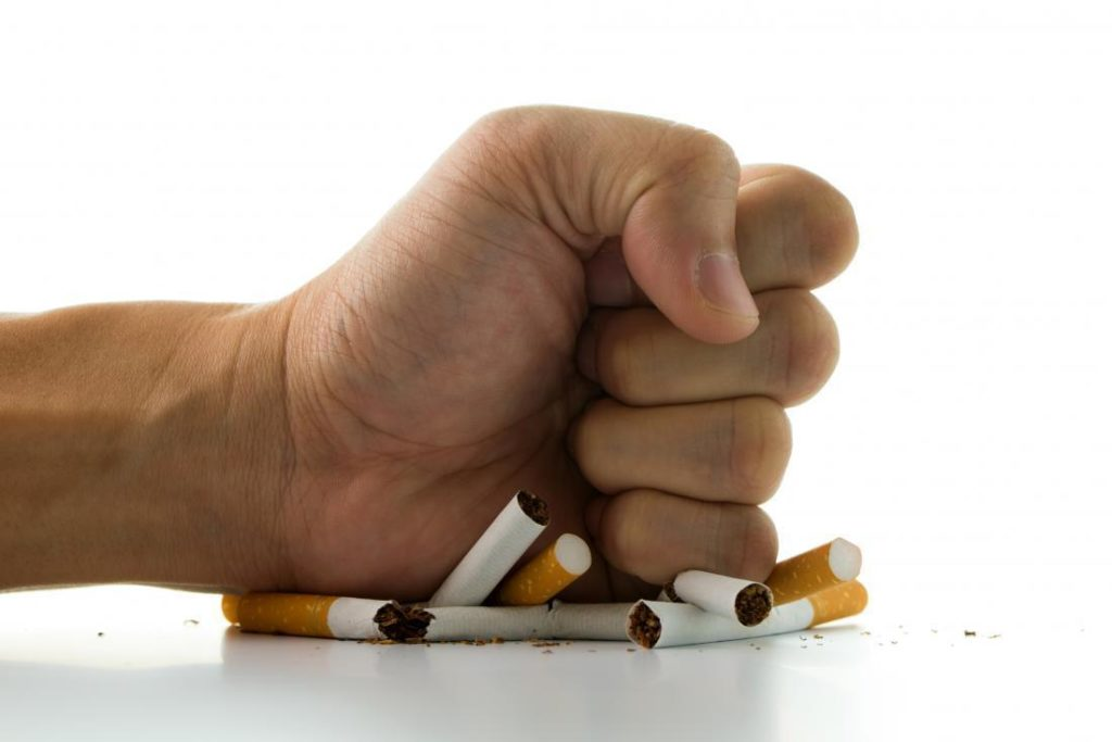 fist on cigar butts - managing cholesterol by quitting smoking