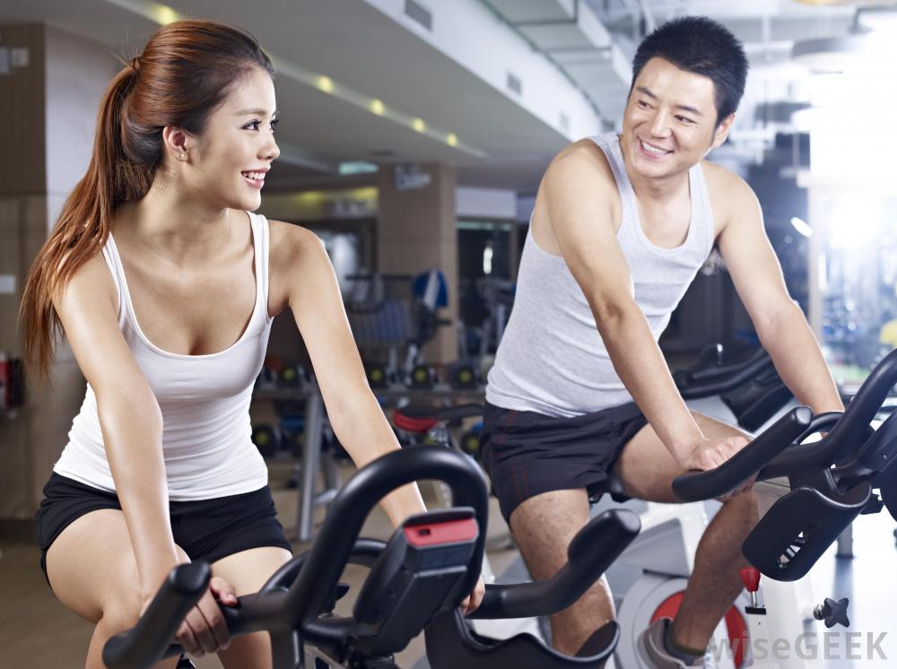 asian-man-and-woman-exercising-on-bike - high cholesterol treatment